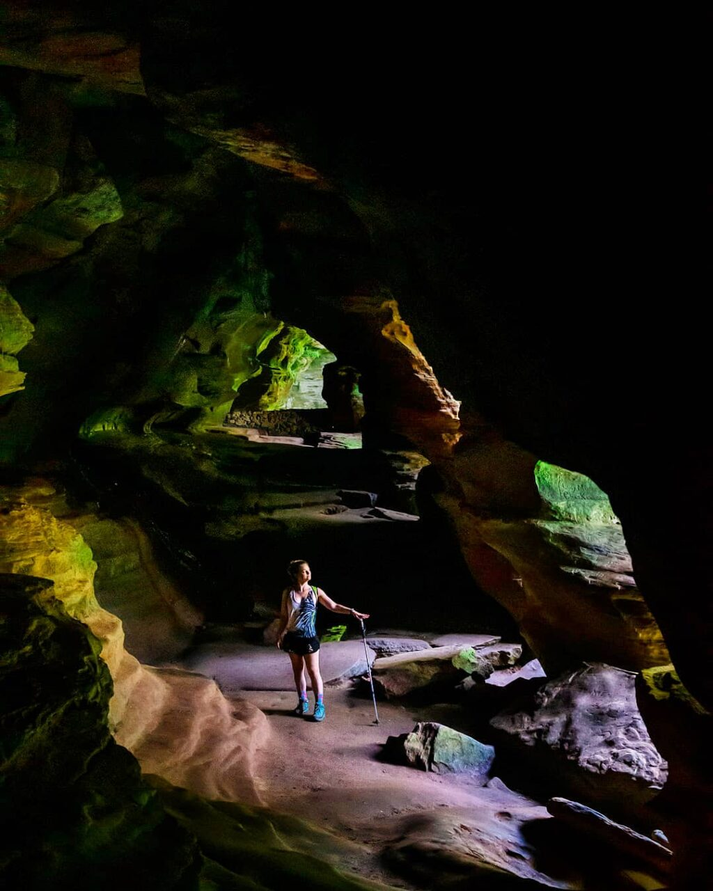 Woman hiker illuminated in the middle of Rock House Cave.