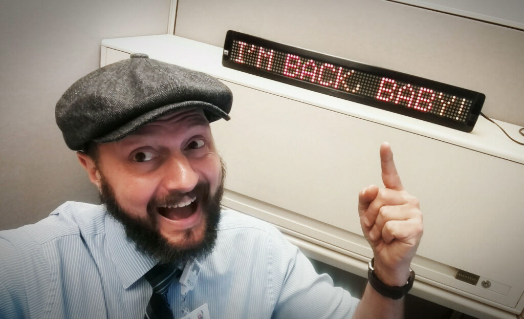 "Andrew in an office cubicle with a digital sign that reads ""I'm back, baby!"""