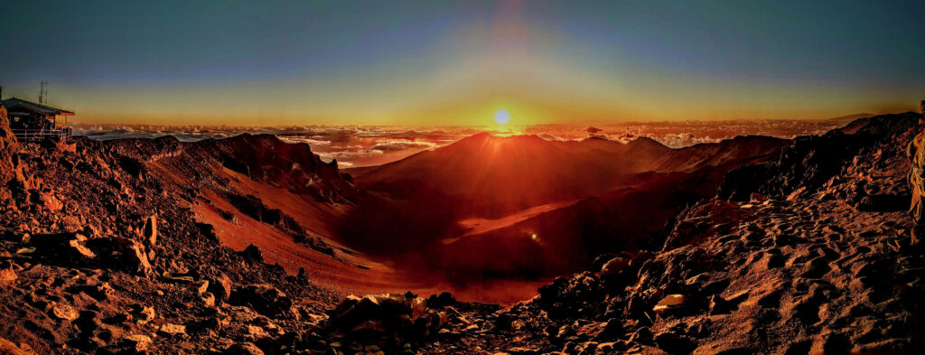 The sun rises above the clouds illuminating the crater at Haleakala National Park.