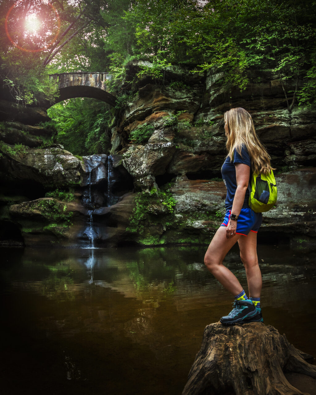 Woman standing on a tree stump with a waterfall in the background in a wooded area.