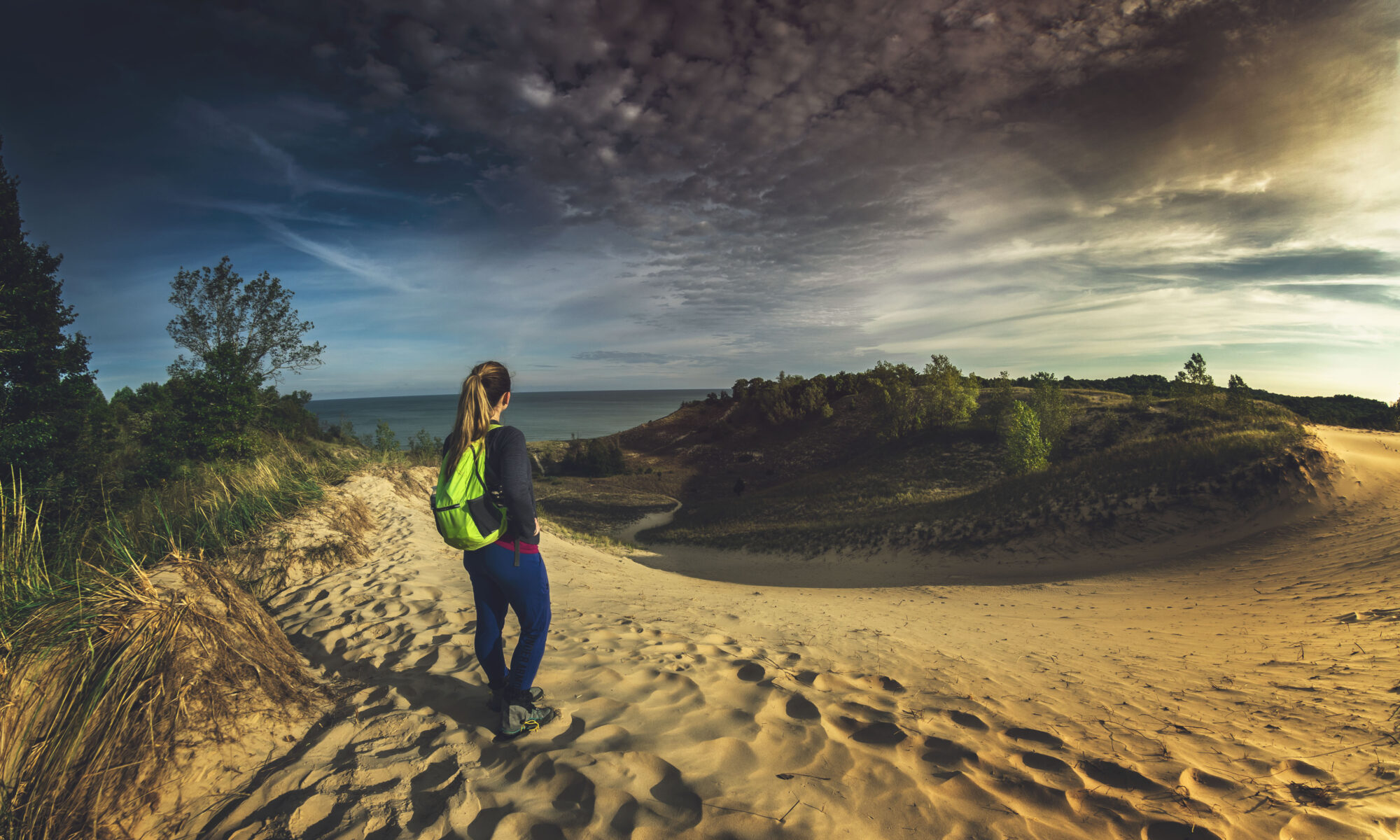 Woman hiker standing atop sand dune overlooking Lake Michigan at Indiana Dunes State Park.