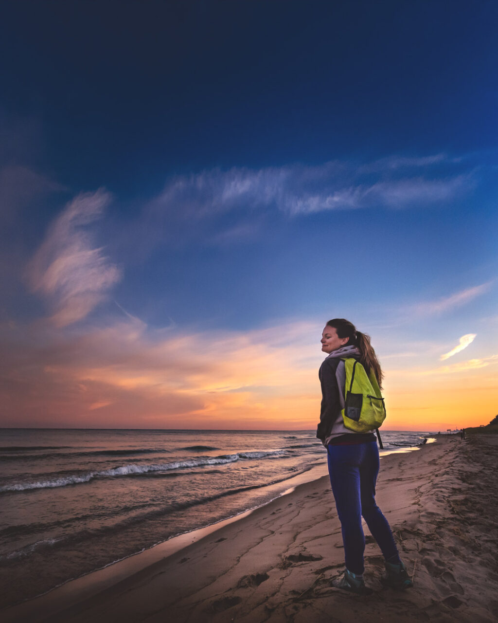 Woman hiker standing on the beach during sunrise at Indiana Dunes.
