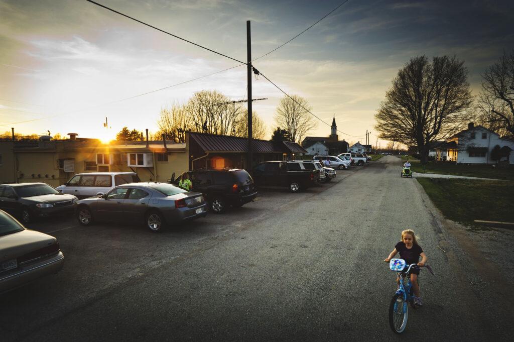 A small girl rides a bike on Enochsburg Road outside the Fireside Inn.