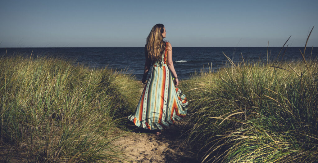 A woman in a colorful dress walks a sandy path in a grassy plain with Lake Michigan in the background.