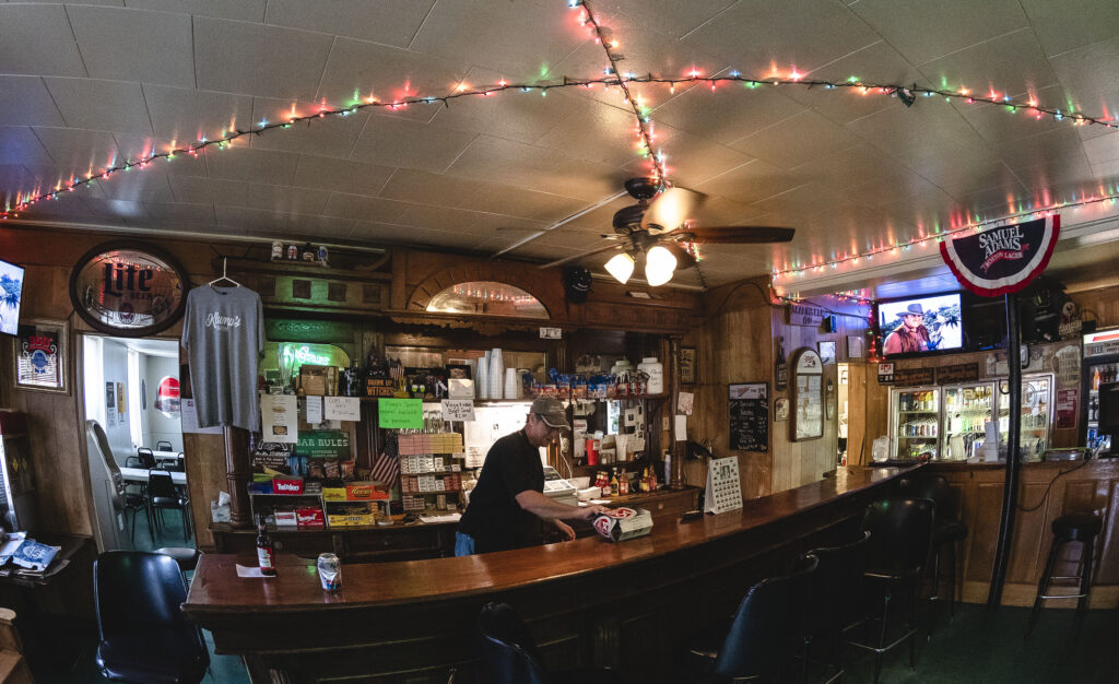 Klump's Tavern interior showing Christmas lights on the ceiling over a bar area.
