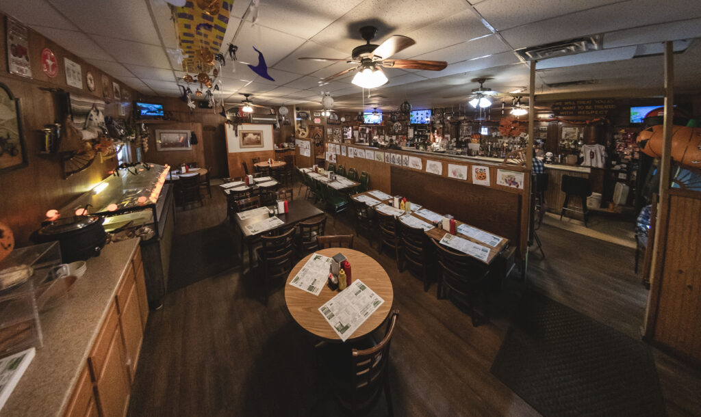 The Pioneer Restaurant interior showing tables, booths and wood paneling.