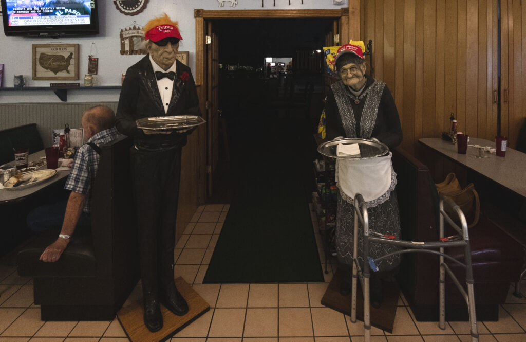 Two mannequins holding serving trays and wearing dress clothes and Trump 2020 baseball caps at Liberty Bell Family Restaurant.