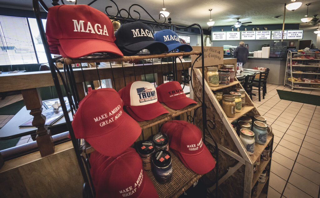 """Rack with several """"MAGA"""" Make America Great Again and Trump hats at Liberty Bell Family Restaurant."""