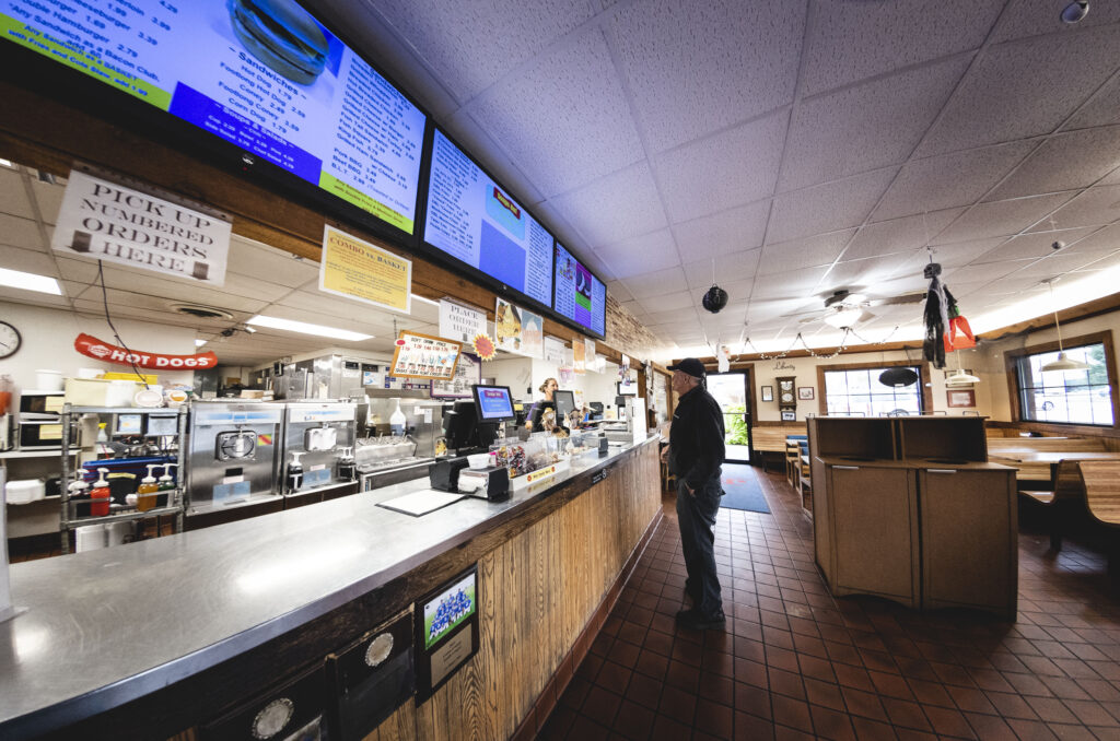 Man standing at the ordering counter at J's Dairy Inn in Liberty, Indiana.