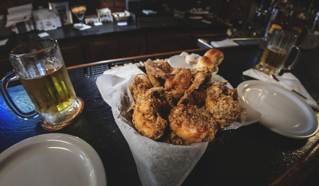 A basket of fried chicken between two plates and two mugs of beer.