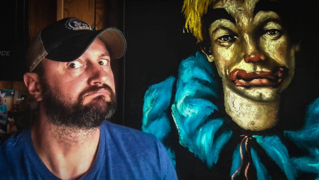 The author poses next to a painting of a clown that hangs in the dining room at Wagner's Village Inn.