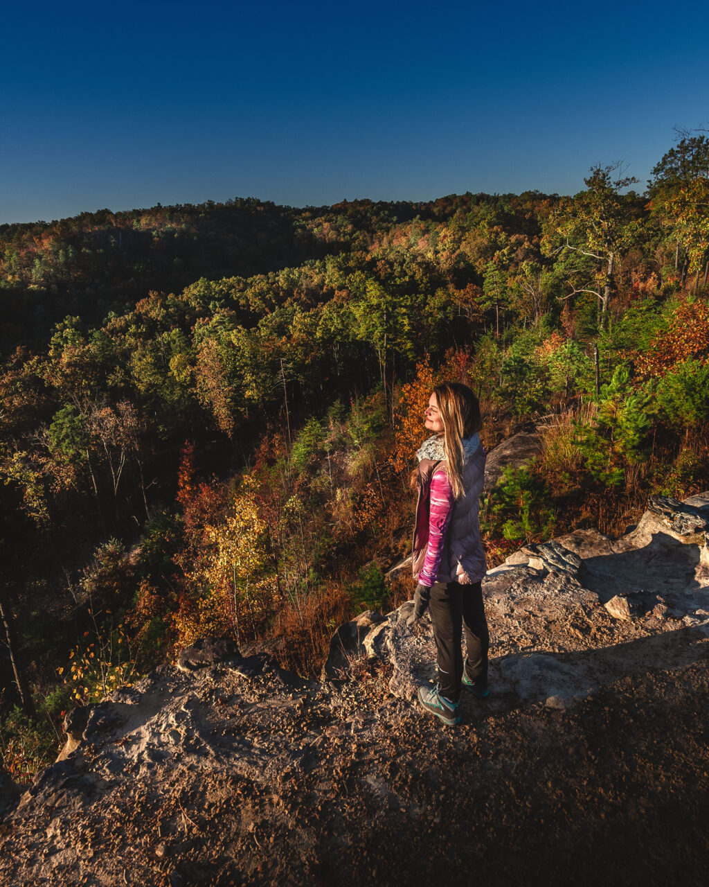 Woman hiker on cliff edge of Auxier Ridge Trail overlooking the trees on the valley floor of Red River Gorge in Kentucky.