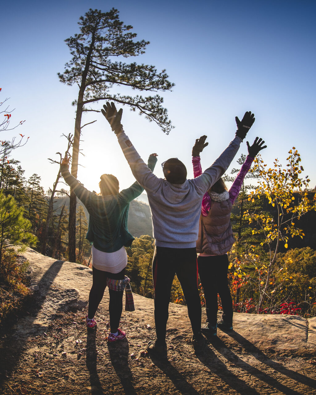 Three hikers facing the sun with arms outstretched above their heads.