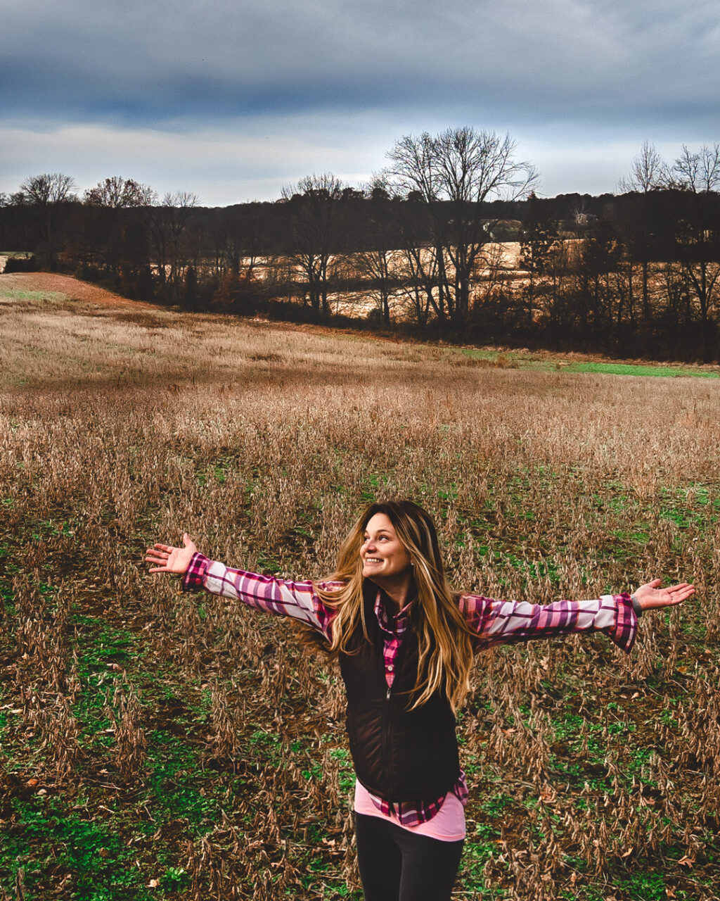 Woman hiker spinning with arms outstretched in a soybean field.