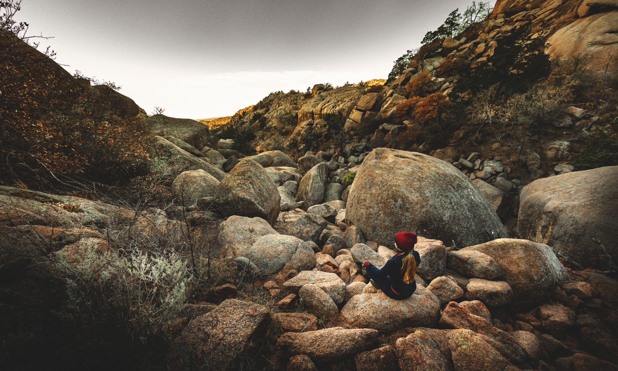 Woman sitting cross-legged overlooking the Valley of Boulders in the Wichita Mountains Wildlife Refuge.