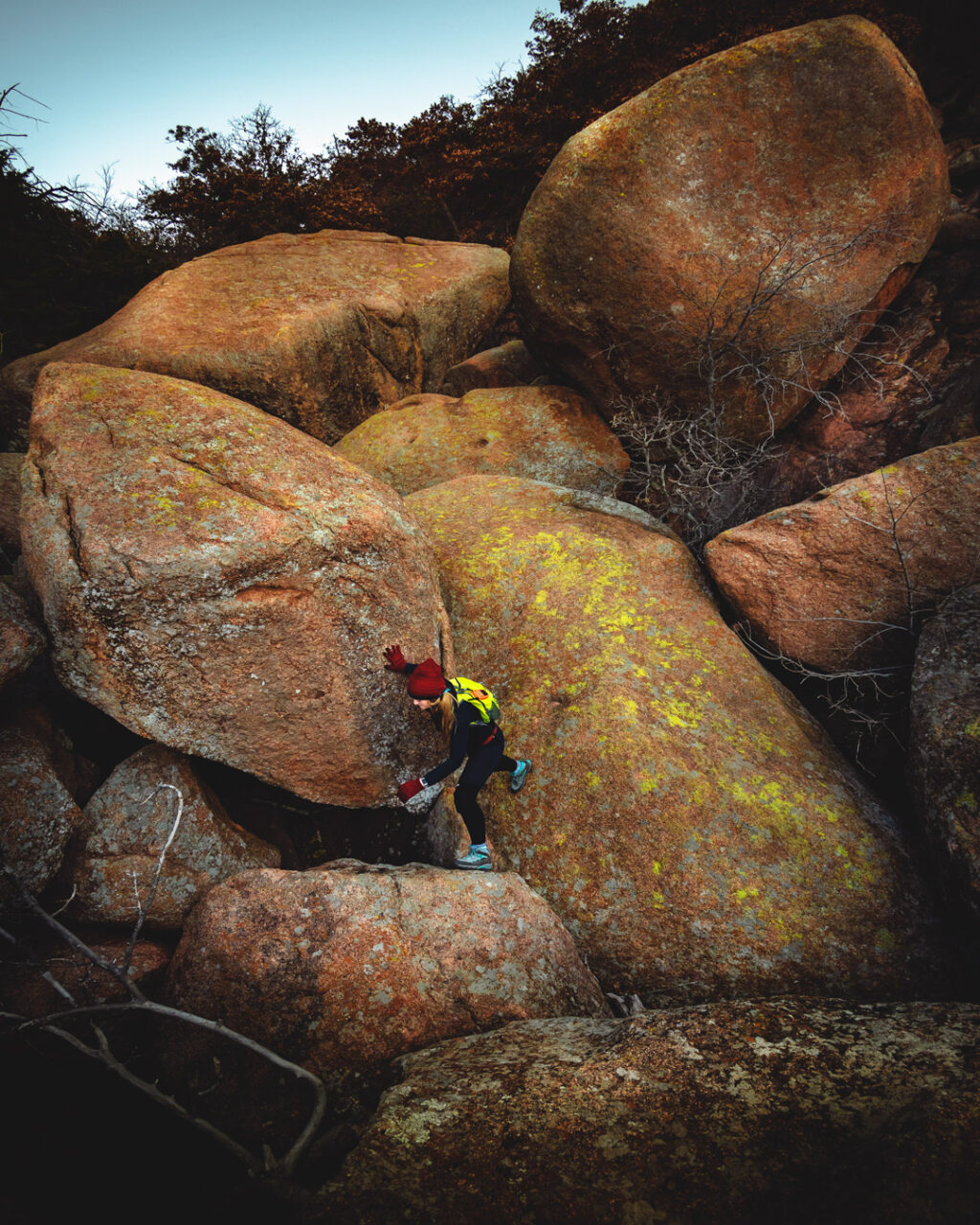Woman hiker navigating massive rocks in the Valley of Boulders at Charon's Garden hiking trail, Wichita Mountains Wildlife Refuge.