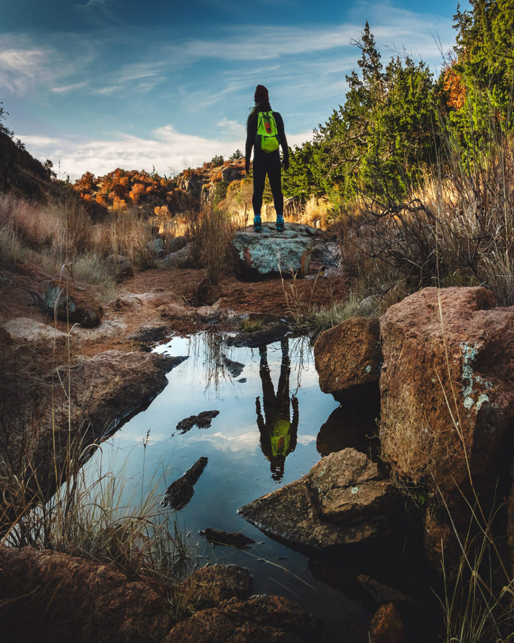 Woman hiker standing atop boulder and reflected in small water pool along Charon's Garden Trail at Wichita Mountains Wildlife Refuge.