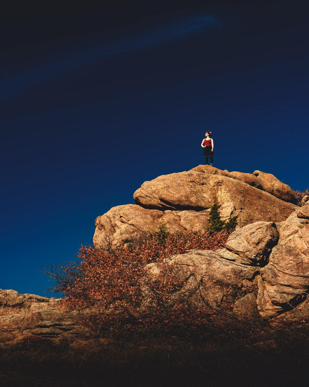 Woman hiker standing atop rocky bluff under blue sky in Charon's Garden Wilderness, Wichita Mountains Wildlife Refuge.