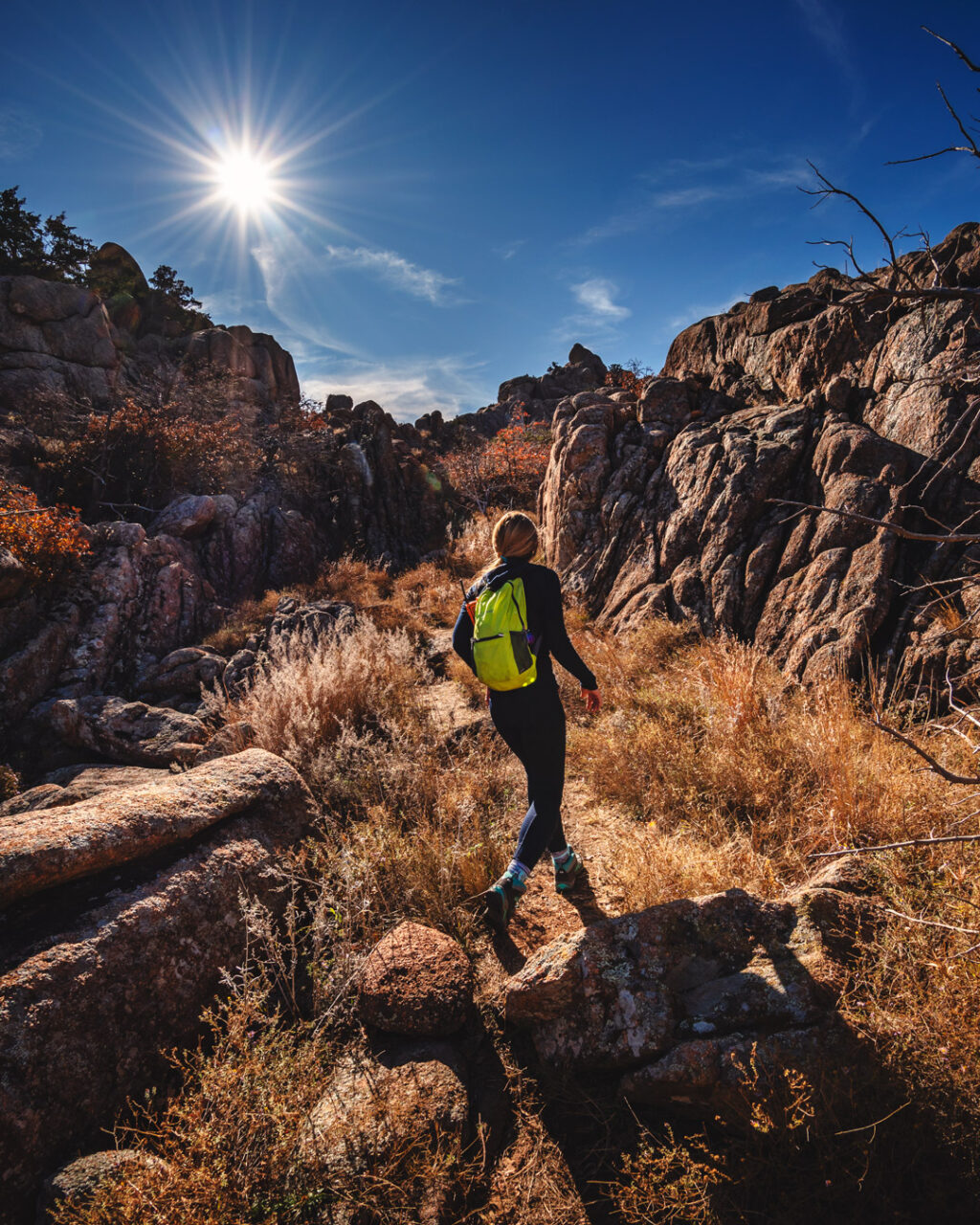 Woman hiking on rocky trails with tall prairie grass under blue sky at Crab Eyes Trail in Wichita Mountains Wildlife Refuge.