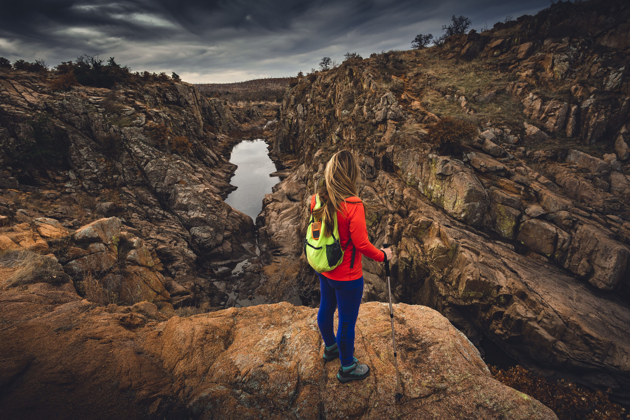 Woman hiker on cliff edge overlooking Forty Foot Hole from Kite Trail Wichita Mountains Wildlife Refuge.