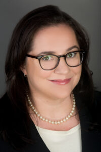 Headshot portrait of Amanda Gaul, Esq., a not-quite-young not-quite-old brunette white woman with dark framed glasses.