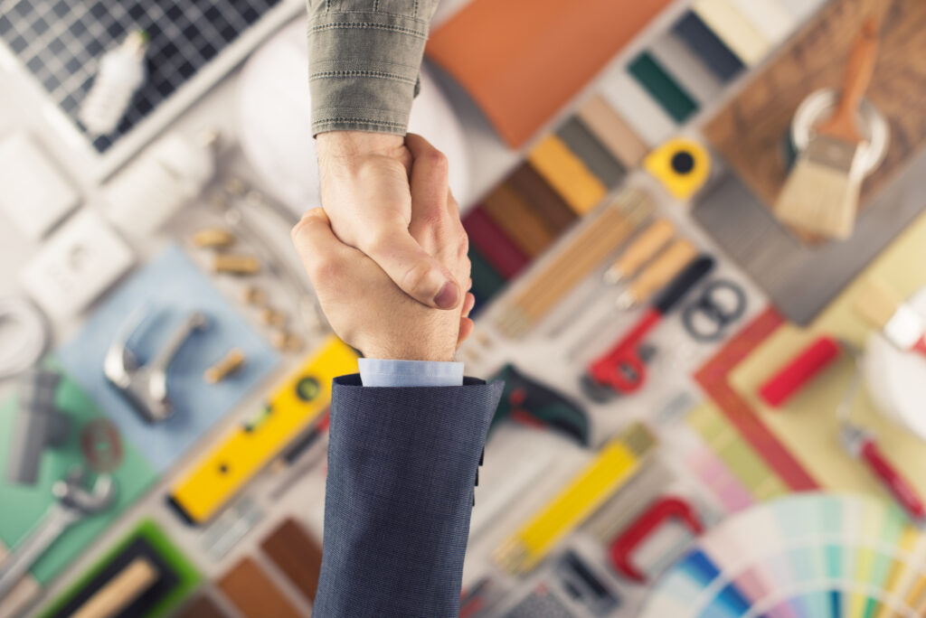 Two men shaking hands over home contractor agreement
