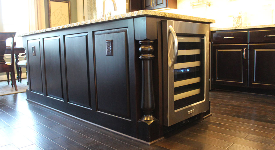 Kitchen Island by Burrows Cabinets in Espresso finish with Monaco corner posts and built in wine refrigerator