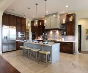Burrows Cabinets kitchen cabinets in stained perimeter cabinets and gray island, Craftsman range hood and Terrazzo doors