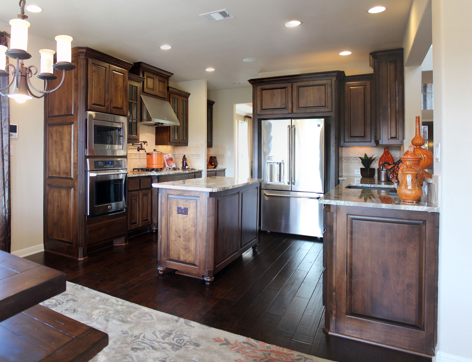 Burrows Cabinets kitchen in stained knotty alder and island with decorative integrated corners and bunn feet