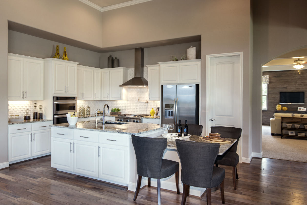 Burrows Cabinets Bone white kitchen with breakfast table in island