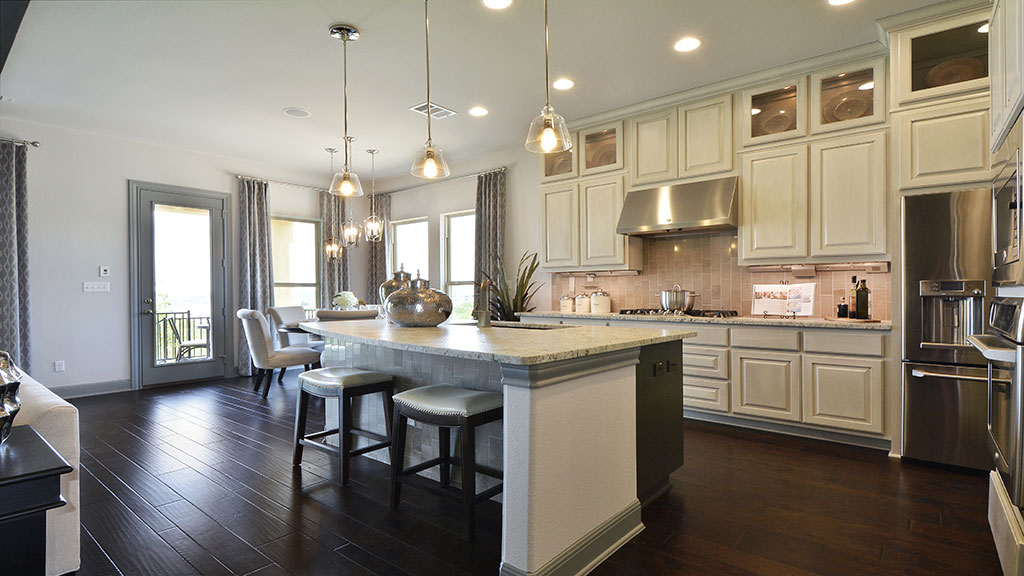 Burrorws Cabinets kitchen in Bone with black glaze and stacked upper cabinets with glass doors