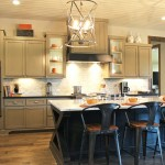 Burrows Cabinets kitchen with black island and gray wall cabinets, wood vent hood and modern crown