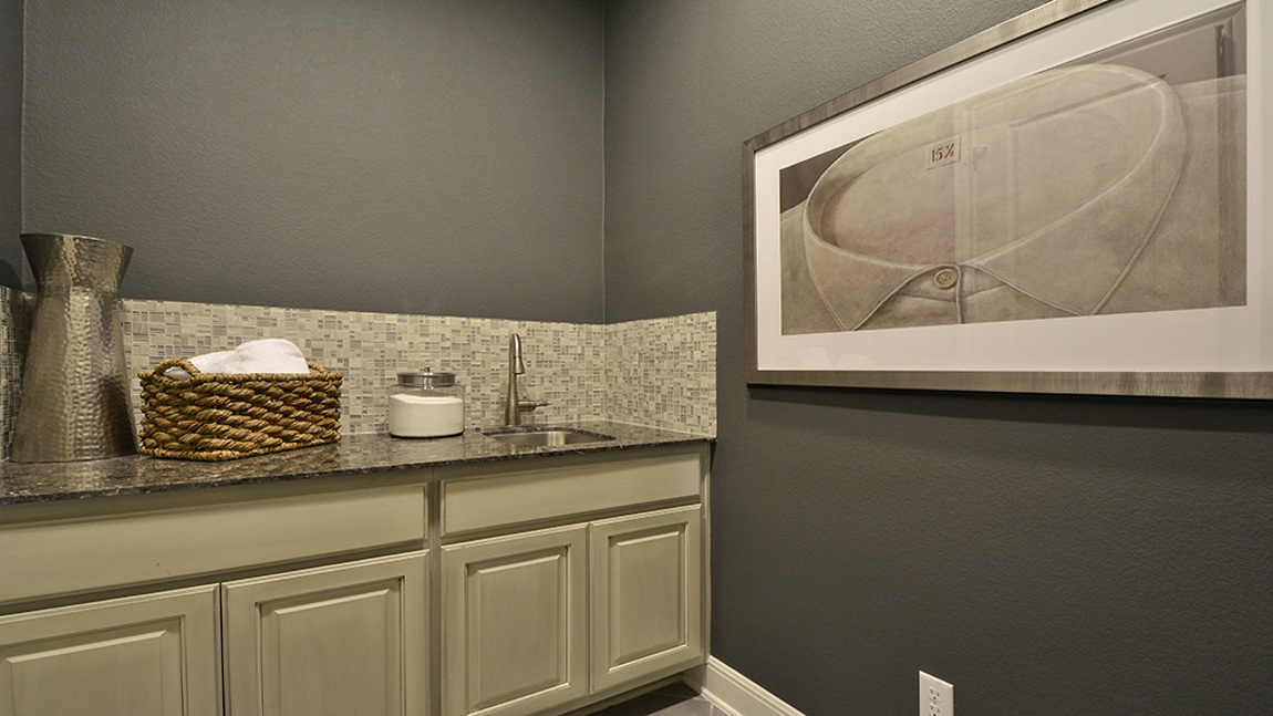 Burrows Cabinets laundry room cabinets in bone with black glaze
