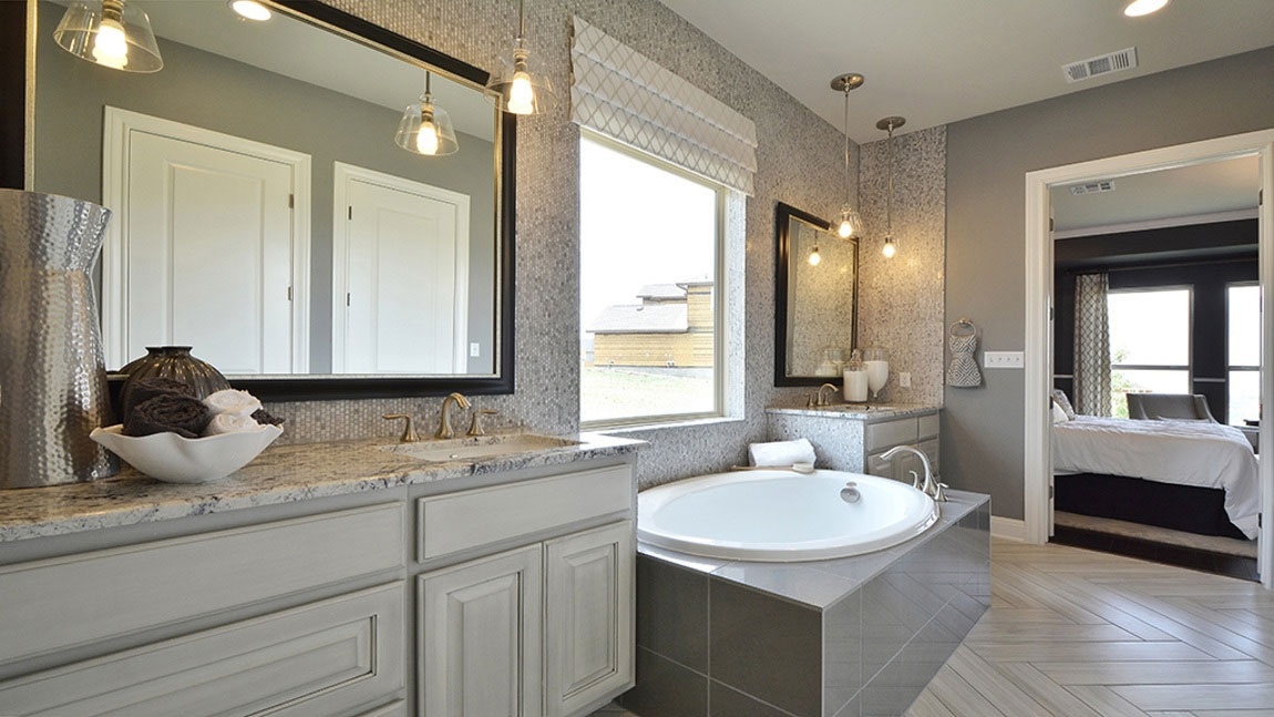 Burrows Cabinets master bath in bone with black glaze and double vanities divided by soaking tub