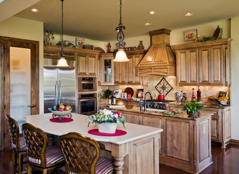 Burrows Cabinets' kitchen with corner posts and custom wood range hood