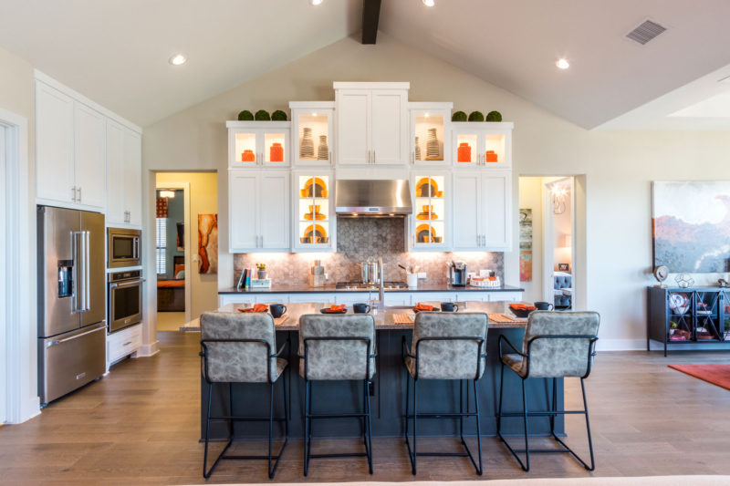 Burrows Cabinets' kitchen with orange accents, Shaker doors in Bone white and Dallas feet