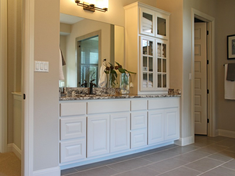 Burrows Cabinets' master bath vanity with glass upper cabinet doors with mullions in bone