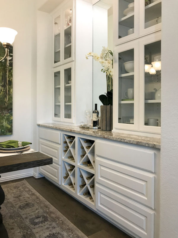 Burrows Cabinets' dining hutch in Frost featuring Big X wine rack, glass and raised panel doors