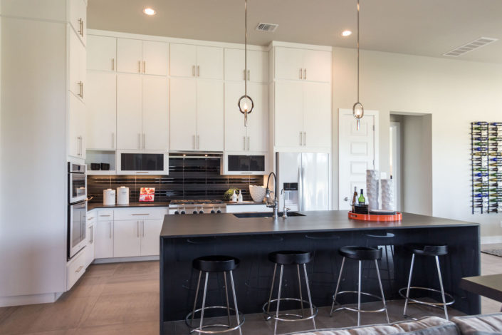 Burrows Cabinets' full overlay kitchen with modern white SoCo doors and black island
