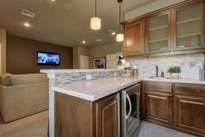 Burrows Cabinets' stained wood wet bar cabinets in Beech with Kona finish with glass door inserts