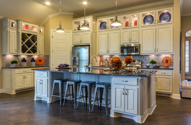 Burrows Cabinets' kitchen in bone with brown glaze with Big X wine rack and integrated corners