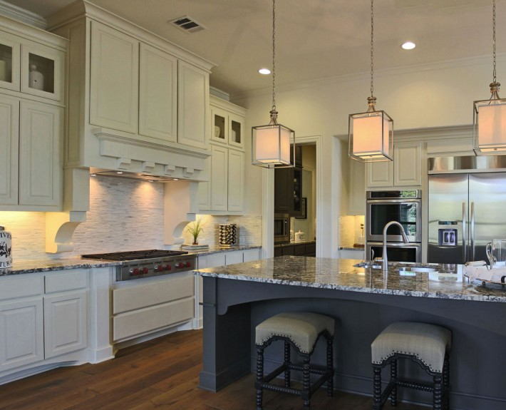 Burrows Cabinets' kitchen in bone white with umber gray island and pantry