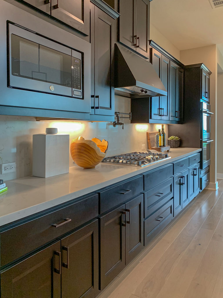 Kitchen cabinets in Beech Espresso by Burrows Cabinets with Briscoe doors and black slate appliances