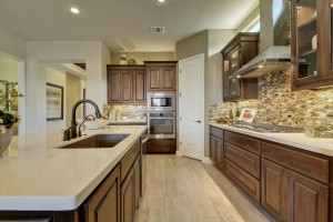 Burrows Cabinets' kitchen cabinets in Beech with Kona stain and glass upper cabinet doors