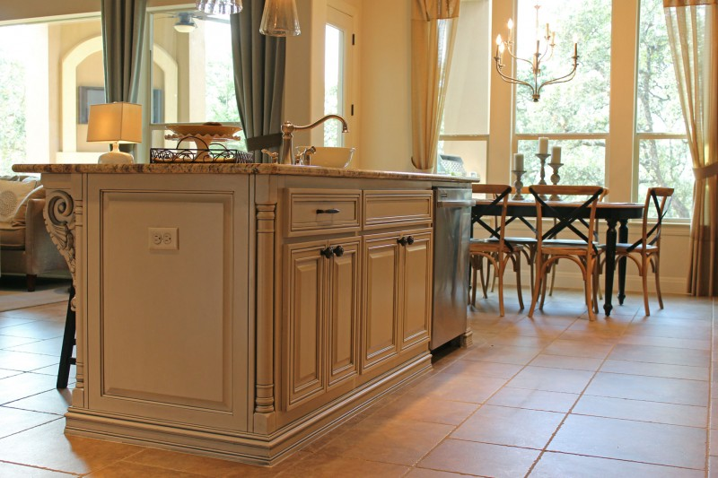 Burrows Cabinets kitchen island in bone with brown glaze and tuscan corner posts