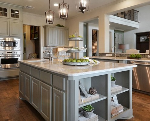 Burrows Cabinets kitchen island in Ecru with bookshelves and integrated corners
