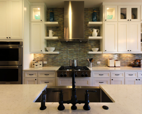 Burrows Cabinets' white kitchen with Terrazzo doors, floating shelves, glass inserts in upper doors