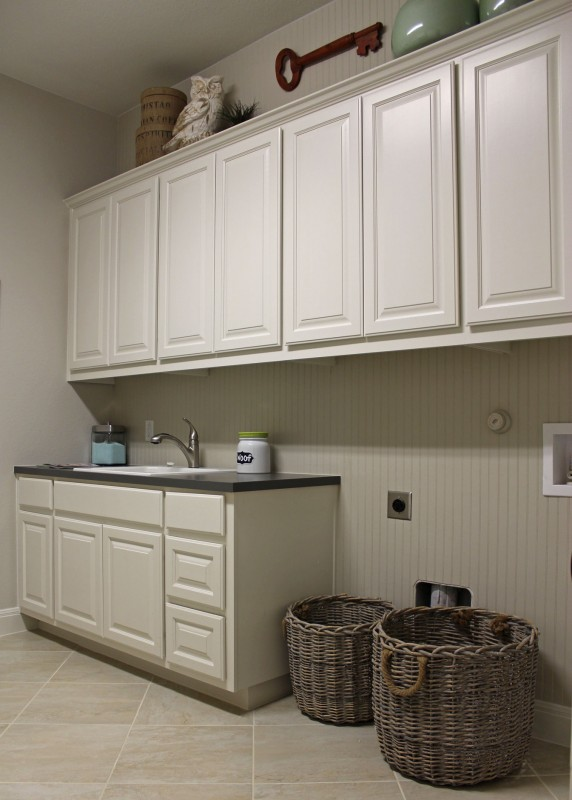 Burrows Cabinets' laundry room cabinets painted white with built-in sink