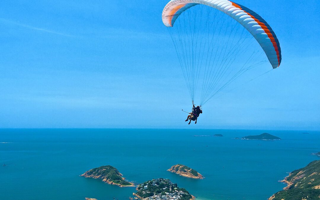 Two people paragliding above a beautiful blue expanse of ocean