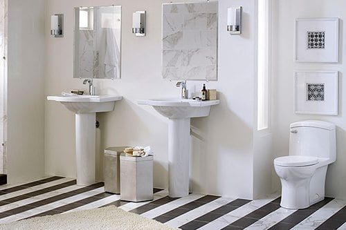 White sinks and toilet on zebra tile floor